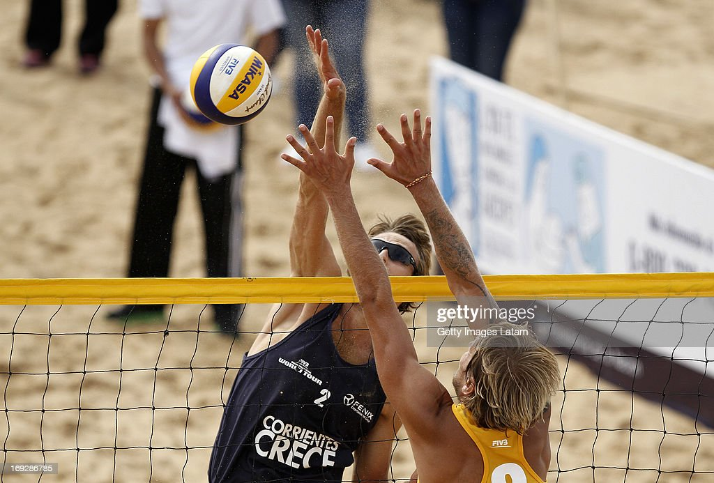 Yaroslav Koshkarev (in Blue) of Russia smashes the ball as <a gi-track='captionPersonalityLinkClicked' href=/galleries/search?phrase=Rivo+Vesik&family=editorial&specificpeople=2335869 ng-click='$event.stopPropagation()'>Rivo Vesik</a> (in yellow) of Estonia tries to block during a match between Russia and Estonia as part of day one of Corrientes Grand Slam of FIVB World Tour at Arazaty Beach on May 22, 2013 in Corrientes, Argentina.