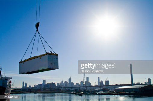 A crane lifts a shipping container over a river past a city skyline.