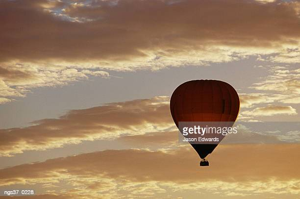 Yarra Valley, Victoria, Australia. A soaring hot air balloon against a cloud-filled sky at dawn.
