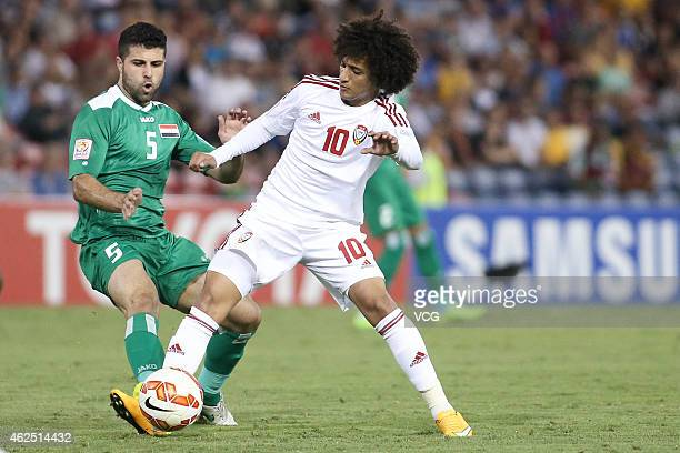 Yaser Safa Kasim of Iraq is pressured by Omar Abdulrahman of Omar Abdulrahman during the Asian Cup thirdplace playoff soccer match between Iraq and...