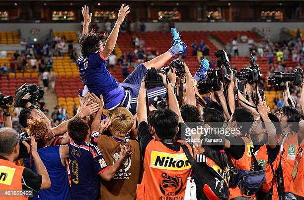 Yashuhito Endo of Japan is thrown into the air by team mates in celebration of his 150th game for Japan during the 2015 Asian Cup match between Iraq...
