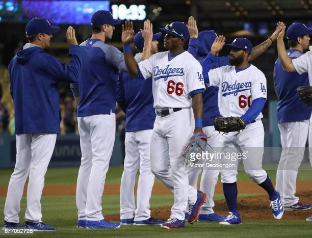 Yasiel Puig and Andrew Toles of the Los Angeles Dodgers and their teammates celebrate in the infield after their 135 MLB game win against the San...