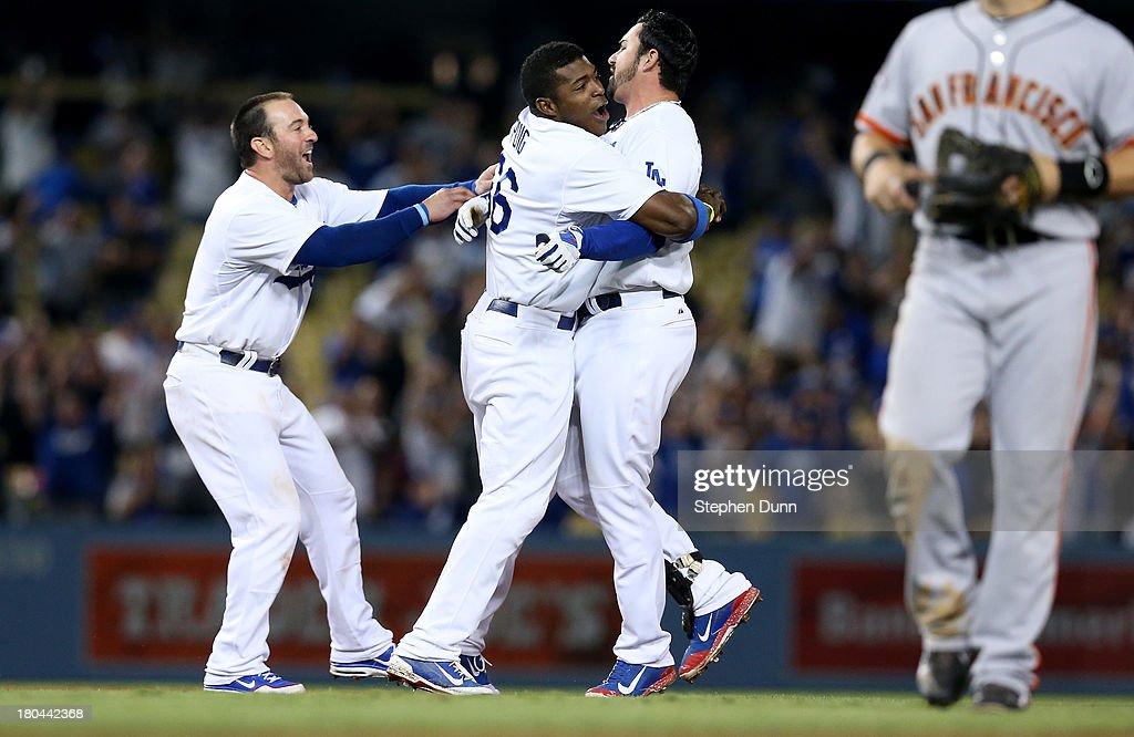 <a gi-track='captionPersonalityLinkClicked' href=/galleries/search?phrase=Yasiel+Puig&family=editorial&specificpeople=10484087 ng-click='$event.stopPropagation()'>Yasiel Puig</a> #66 and <a gi-track='captionPersonalityLinkClicked' href=/galleries/search?phrase=Nick+Punto&family=editorial&specificpeople=547246 ng-click='$event.stopPropagation()'>Nick Punto</a> #7 of the Los Angeles Dodgers hug Adrian Gonzalez #23 (R) after Gonzalez' walk off RBI single against the San Francisco Giants at Dodger Stadium on September 12, 2013 in Los Angeles, California. The Dodgers won 3-2 in ten innings.