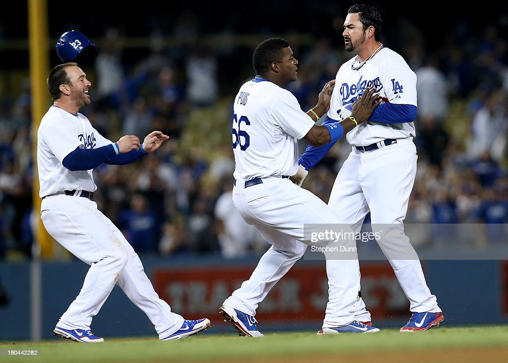 <a gi-track='captionPersonalityLinkClicked' href=/galleries/search?phrase=Yasiel+Puig&family=editorial&specificpeople=10484087 ng-click='$event.stopPropagation()'>Yasiel Puig</a> #66 and <a gi-track='captionPersonalityLinkClicked' href=/galleries/search?phrase=Nick+Punto&family=editorial&specificpeople=547246 ng-click='$event.stopPropagation()'>Nick Punto</a> #7 of the Los Angeles Dodgers run out to greet Adrian Gonzalez #23 (R) after Gonzalez' walk off RBI single against the San Francisco Giants at Dodger Stadium on September 12, 2013 in Los Angeles, California. The Dodgers won 3-2 in ten innings.