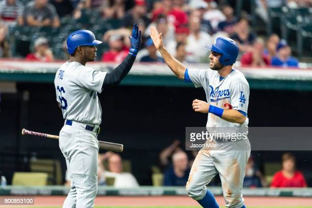 Yasiel Puig celebrates with Chris Taylor of the Los Angeles Dodgers after Taylor scores during the eighth inning against the Cleveland Indians at...