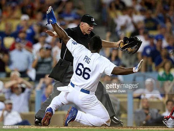 Yasiel Puig of the Los Angeles Dodgers and home plate umpire Ed Hickox both give the safe sign after Puig slid home with a run on a sacrifice fly in...