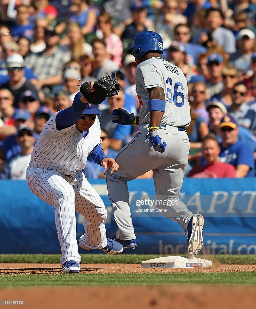 <a gi-track='captionPersonalityLinkClicked' href=/galleries/search?phrase=Yasiel+Puig&family=editorial&specificpeople=10484087 ng-click='$event.stopPropagation()'>Yasiel Puig</a> #66 of the Los Angeles Dodgers beats a throw at first base to <a gi-track='captionPersonalityLinkClicked' href=/galleries/search?phrase=Anthony+Rizzo&family=editorial&specificpeople=7551494 ng-click='$event.stopPropagation()'>Anthony Rizzo</a> #44 of the Chicago Cubs at Wrigley Field on August 3, 2013 in Chicago, Illinois. The Dodgers defeated the Cubs 3-0.