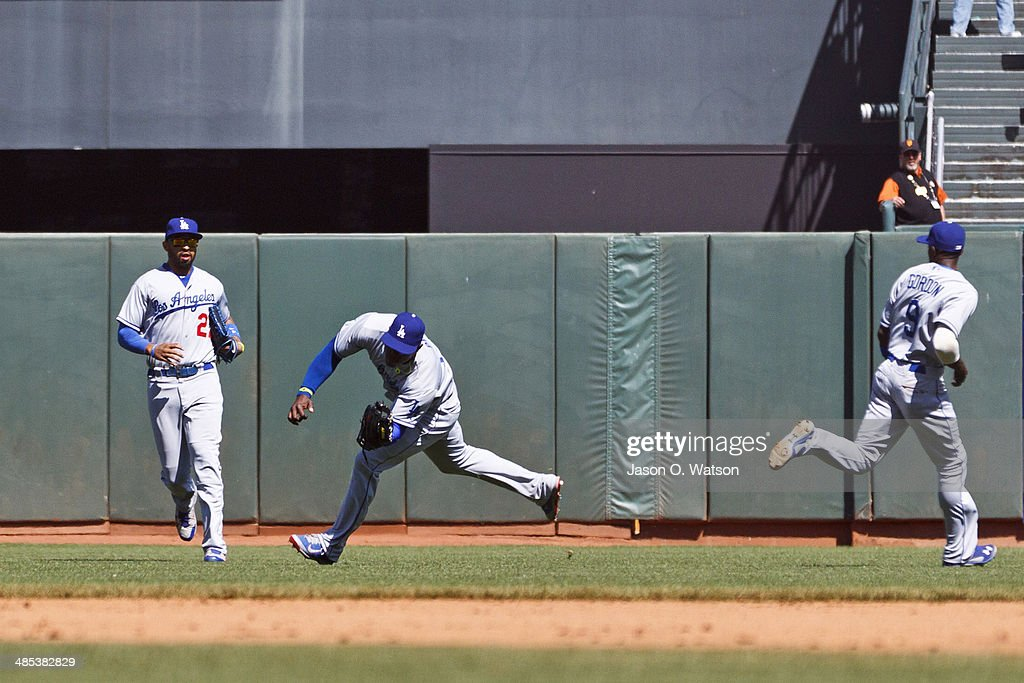 <a gi-track='captionPersonalityLinkClicked' href=/galleries/search?phrase=Yasiel+Puig&family=editorial&specificpeople=10484087 ng-click='$event.stopPropagation()'>Yasiel Puig</a> #66 of the Los Angeles Dodgers catches a fly ball off the bat of Joaquin Arias (not pictured) of the San Francisco Giants in front of <a gi-track='captionPersonalityLinkClicked' href=/galleries/search?phrase=Matt+Kemp&family=editorial&specificpeople=567161 ng-click='$event.stopPropagation()'>Matt Kemp</a> #27 and <a gi-track='captionPersonalityLinkClicked' href=/galleries/search?phrase=Dee+Gordon&family=editorial&specificpeople=7091343 ng-click='$event.stopPropagation()'>Dee Gordon</a> #9 during the eighth inning at AT&T Park on April 17, 2014 in San Francisco, California.