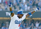 Yasiel Puig of the Los Angeles Dodgers celebrates as he runs to first after hitting a walk off solo home run in the 11th inning against the...
