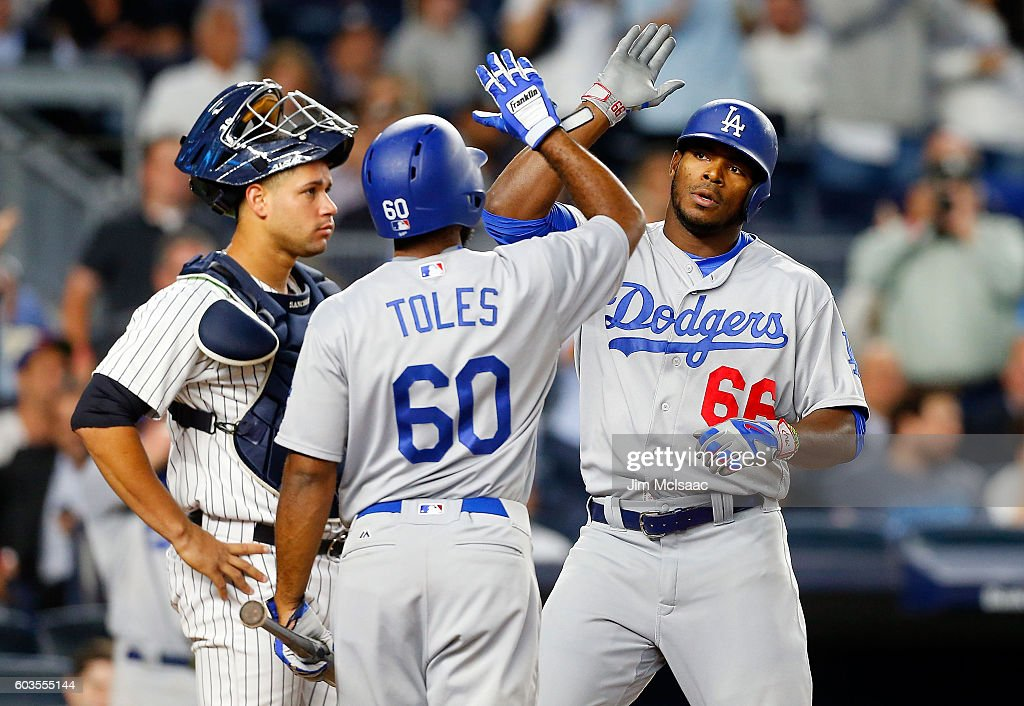 Yasiel Puig #66 of the Los Angeles Dodgers celebrates his eighth inning home run with teammate Andrew Toles #60 as Gary Sanchez #24 of the New York Yankees looks on at Yankee Stadium on September 12, 2016 in the Bronx borough of New York City.