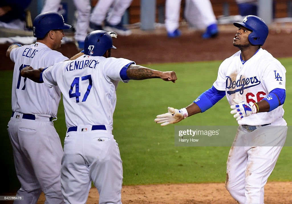 Yasiel Puig #66 of the Los Angeles Dodgers celebrates his inside the park homerun with A.J. Ellis #17 and Howie Kendrick #47 to win the game 4-3 over the Washington Nationals during the ninth inning at Dodger Stadium on June 22, 2016 in Los Angeles, California.