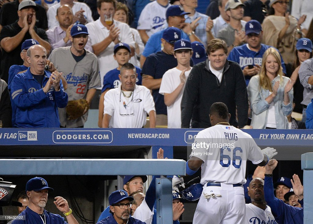 <a gi-track='captionPersonalityLinkClicked' href=/galleries/search?phrase=Yasiel+Puig&family=editorial&specificpeople=10484087 ng-click='$event.stopPropagation()'>Yasiel Puig</a> #66 of the Los Angeles Dodgers celebrates his sacrifice fly to score Adrian Gonzalez #23 to take a 3-2 lead over the New York Mets during the sixth inning at Dodger Stadium on August 12, 2013 in Los Angeles, California.