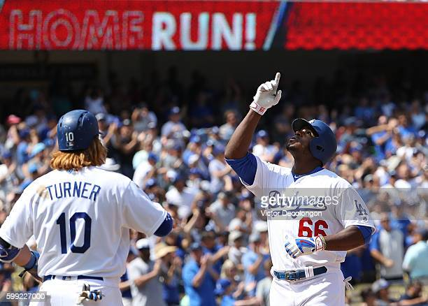 Yasiel Puig of the Los Angeles Dodgers celebrates his threerun homerun at home plate as teammate Justin Turner awaits Puig during the third inning of...