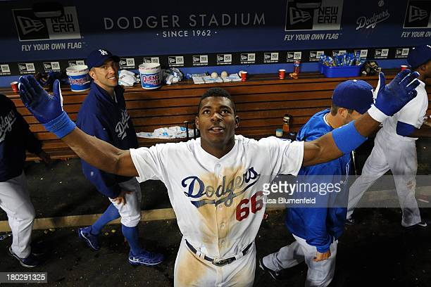 Yasiel Puig of the Los Angeles Dodgers celebrates in the dugout after defeating the Arizona Diamondbacks 53 in eleven innings at Dodger Stadium on...