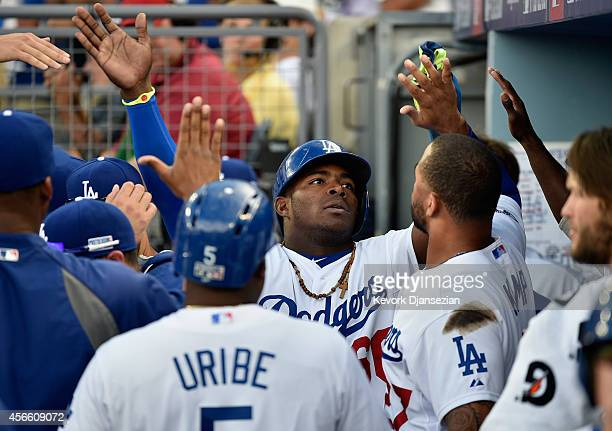 Yasiel Puig of the Los Angeles Dodgers celebrates in the dugout after scoting on a single by teammate Hanley Ramirez in the third inning during Game...