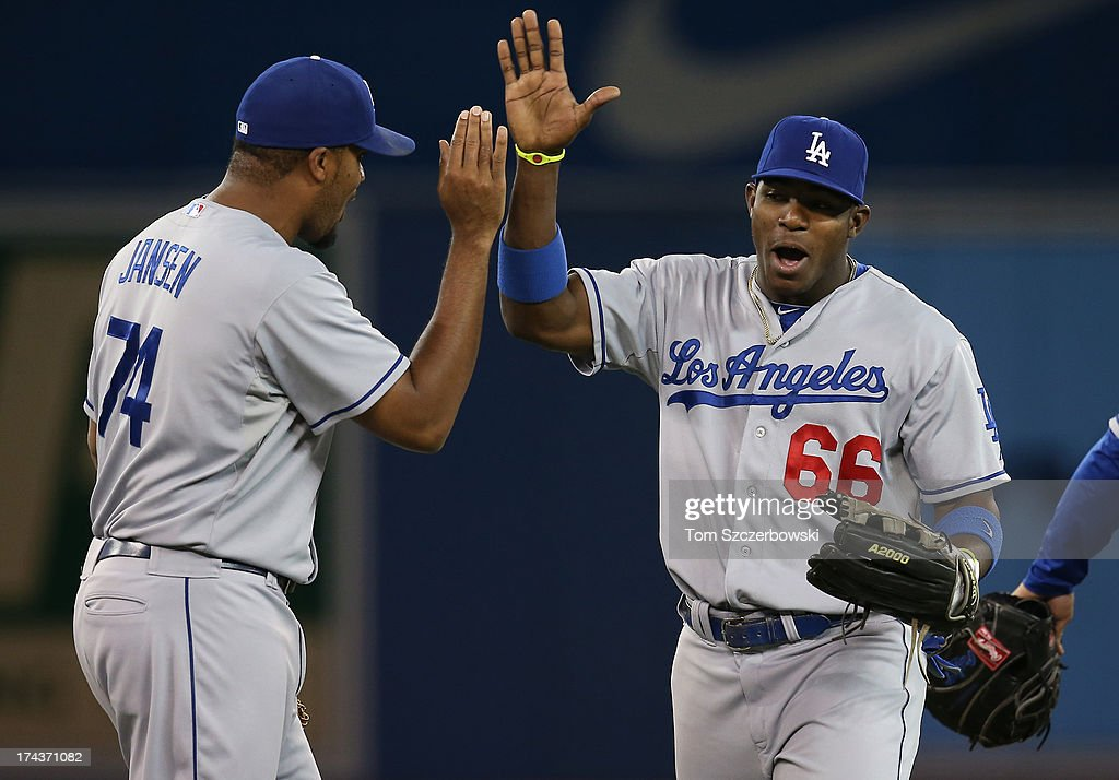 <a gi-track='captionPersonalityLinkClicked' href=/galleries/search?phrase=Yasiel+Puig&family=editorial&specificpeople=10484087 ng-click='$event.stopPropagation()'>Yasiel Puig</a> #66 of the Los Angeles Dodgers celebrates their victory with <a gi-track='captionPersonalityLinkClicked' href=/galleries/search?phrase=Kenley+Jansen&family=editorial&specificpeople=5751411 ng-click='$event.stopPropagation()'>Kenley Jansen</a> #74 during MLB game action against the Toronto Blue Jays on July 24, 2013 at Rogers Centre in Toronto, Ontario, Canada.