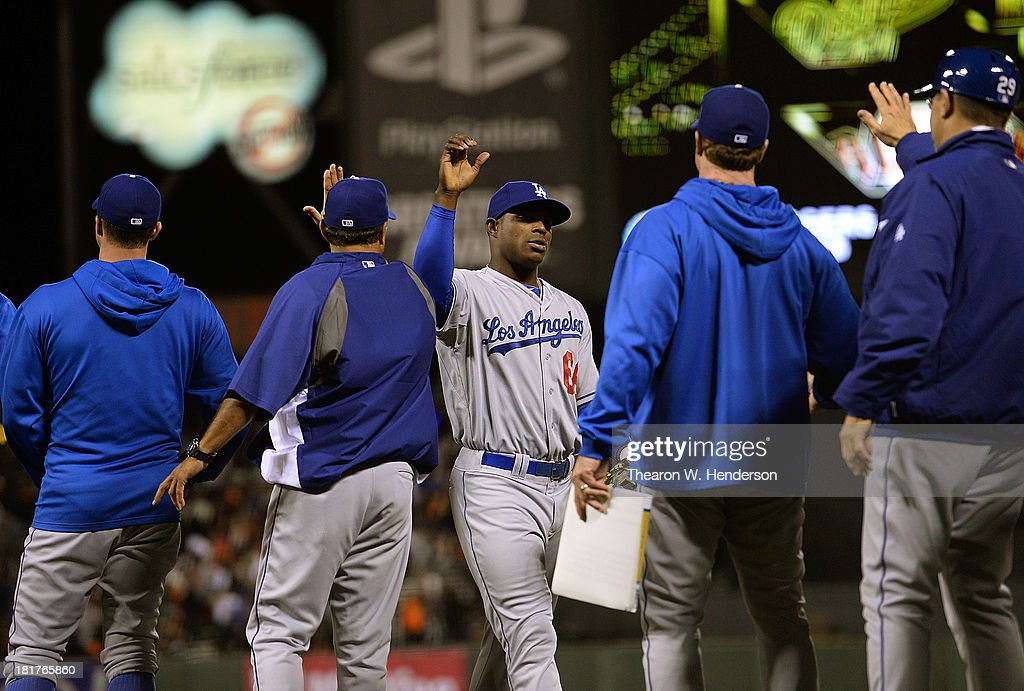 Yasiel Puig #66 of the Los Angeles Dodgers celebrates with teammates and coaches after they defeated the San Francisco Giants 2-1 at AT&T Park on September 24, 2013 in San Francisco, California.