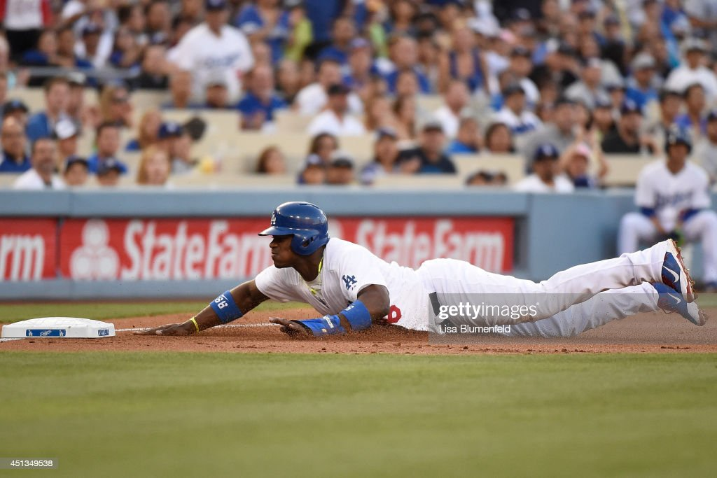 Yasiel Puig of the Los Angeles Dodgers dives safely to third base in the first inning against the St Louis Cardinals at Dodger Stadium on June 27...