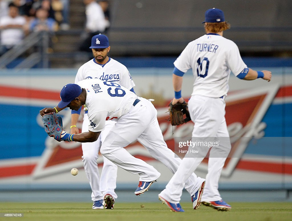Yasiel Puig #66 of the Los Angeles Dodgers drops a ball off the bat of Jimmy Rollins #11 of the Philadelphia Phillies resulting in a single as Matt Kemp #27 and Justin Turner #10 watch during the first inning at Dodger Stadium on April 21, 2014 in Los Angeles, California.