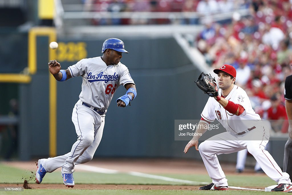 <a gi-track='captionPersonalityLinkClicked' href=/galleries/search?phrase=Yasiel+Puig&family=editorial&specificpeople=10484087 ng-click='$event.stopPropagation()'>Yasiel Puig</a> #66 of the Los Angeles Dodgers gets back to first base ahead of the throw to <a gi-track='captionPersonalityLinkClicked' href=/galleries/search?phrase=Joey+Votto&family=editorial&specificpeople=759319 ng-click='$event.stopPropagation()'>Joey Votto</a> #19 of the Cincinnati Reds in the first inning of the game at Great American Ball Park on September 6, 2013 in Cincinnati, Ohio.