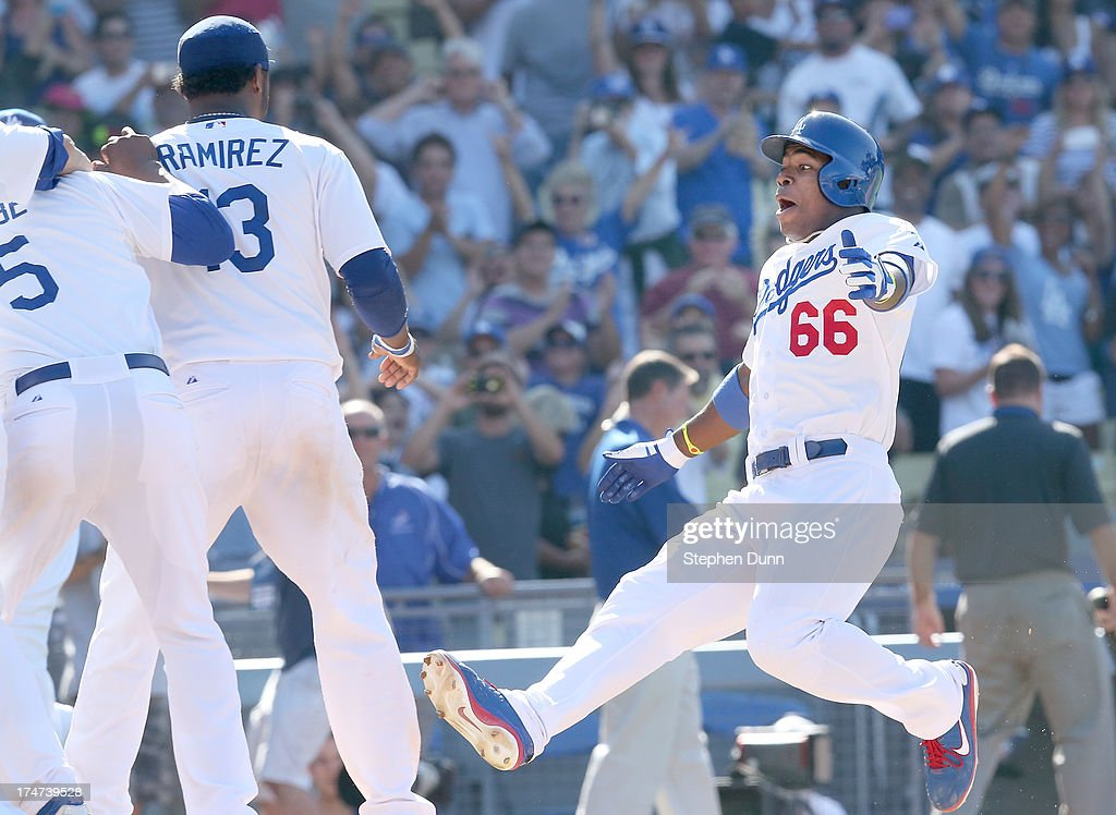 Yasiel Puig #66 of the Los Angeles Dodgers goes into a slide as he comes home to his teammates after hitting a walk off solo home run in the 11th inning against the Cincinnati Reds at Dodger Stadium on July 28, 2013 in Los Angeles, California. The dsosdgers won 1-0 in 11 innings.
