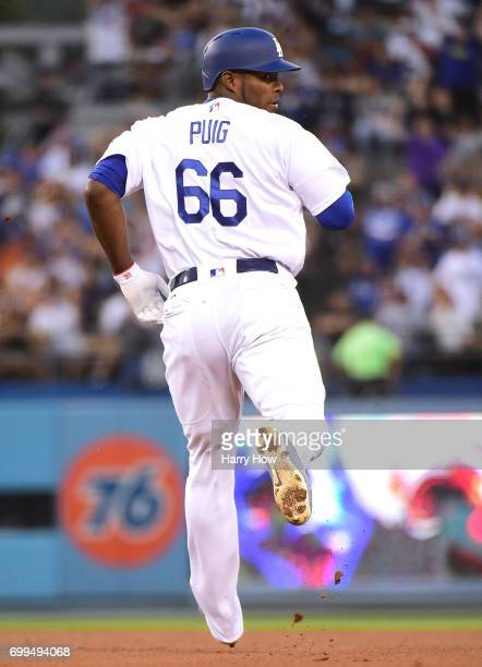 Yasiel Puig of the Los Angeles Dodgers heads to second base as he watches a throwing error from TJ Rivera of the New York Mets during the third...