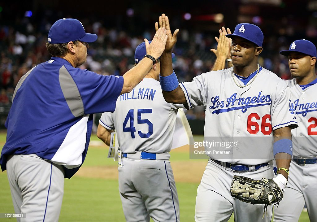 Yasiel Puig #66 of the Los Angeles Dodgers high-fives pitching coach Rick Honeycutt after defeating the Arizona Diamondbacks in the MLB game at Chase Field on July 8, 2013 in Phoenix, Arizona. The Dodgers defeated the Diamondbacks 6-1.
