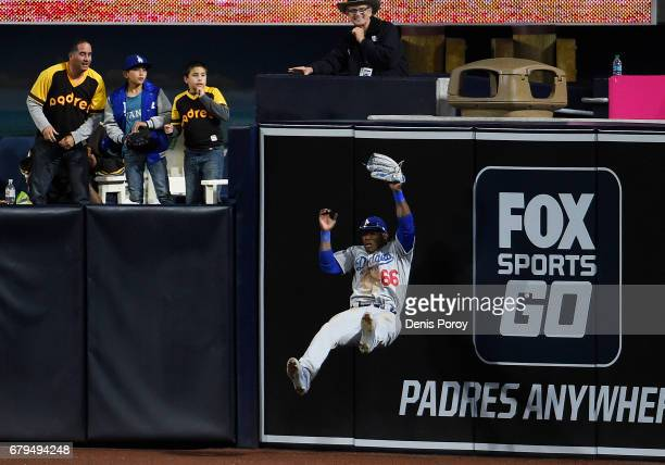 Yasiel Puig of the Los Angeles Dodgers hits the wall as he makes the catch on a ball hit by Austin Hedges of the San Diego Padres during the eighth...