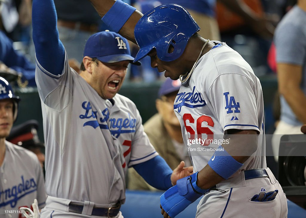 <a gi-track='captionPersonalityLinkClicked' href=/galleries/search?phrase=Yasiel+Puig&family=editorial&specificpeople=10484087 ng-click='$event.stopPropagation()'>Yasiel Puig</a> #66 of the Los Angeles Dodgers is congratulated by <a gi-track='captionPersonalityLinkClicked' href=/galleries/search?phrase=Nick+Punto&family=editorial&specificpeople=547246 ng-click='$event.stopPropagation()'>Nick Punto</a> #7 after scoring the tying run in the ninth inning during MLB game action against the Toronto Blue Jays on July 24, 2013 at Rogers Centre in Toronto, Ontario, Canada.