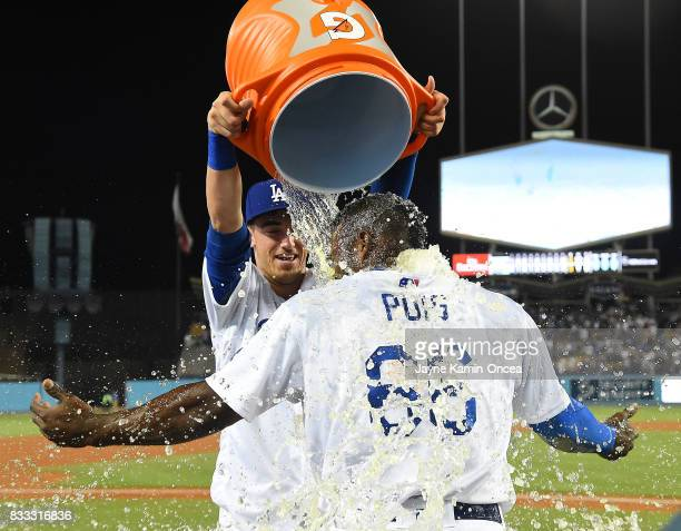 Yasiel Puig of the Los Angeles Dodgers is doused with ice water by Cody Bellinger after hitting a walk off three run home run in the ninth inning of...