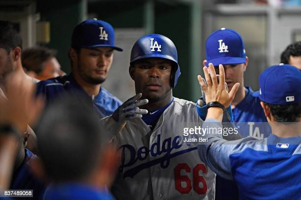 Yasiel Puig of the Los Angeles Dodgers is greeted by teammates after coming around to score on a RBI single by Chris Taylor in the fourth inning...