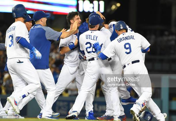 Yasiel Puig of the Los Angeles Dodgers is mobbed by team mates as they celebrate his walk off three run home run to defeat the Chicago White Sox in...