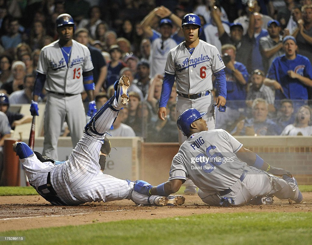 <a gi-track='captionPersonalityLinkClicked' href=/galleries/search?phrase=Yasiel+Puig&family=editorial&specificpeople=10484087 ng-click='$event.stopPropagation()'>Yasiel Puig</a> #66 of the Los Angeles Dodgers is tagged out at home plate by <a gi-track='captionPersonalityLinkClicked' href=/galleries/search?phrase=Dioner+Navarro&family=editorial&specificpeople=593062 ng-click='$event.stopPropagation()'>Dioner Navarro</a> #30 of the Chicago Cubs during the sixth inning on August 1, 2013 at Wrigley Field in Chicago, Illinois.