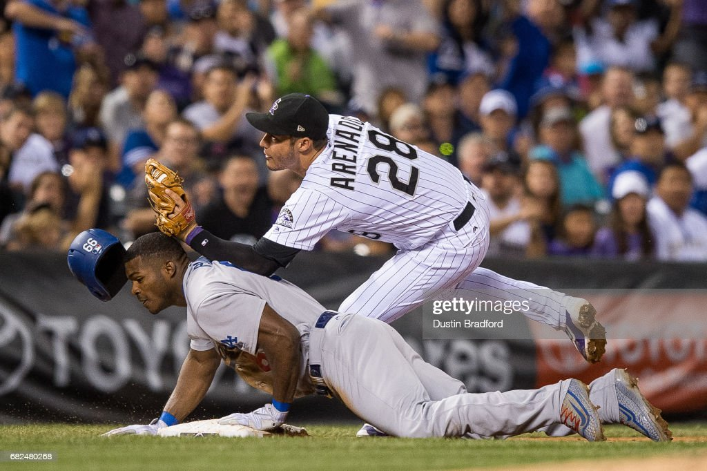 Yasiel Puig #66 of the Los Angeles Dodgers is tagged out at third base by Nolan Arenado #28 of the Colorado Rockies after trying to stretch a double in the sixth inning of a game at Coors Field on May 12, 2017 in Denver, Colorado.