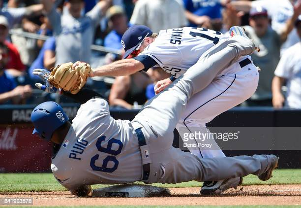 Yasiel Puig of the Los Angeles Dodgers is tagged out at third base by Cory Spangenberg of the San Diego Padres as he tries to stretch a double during...