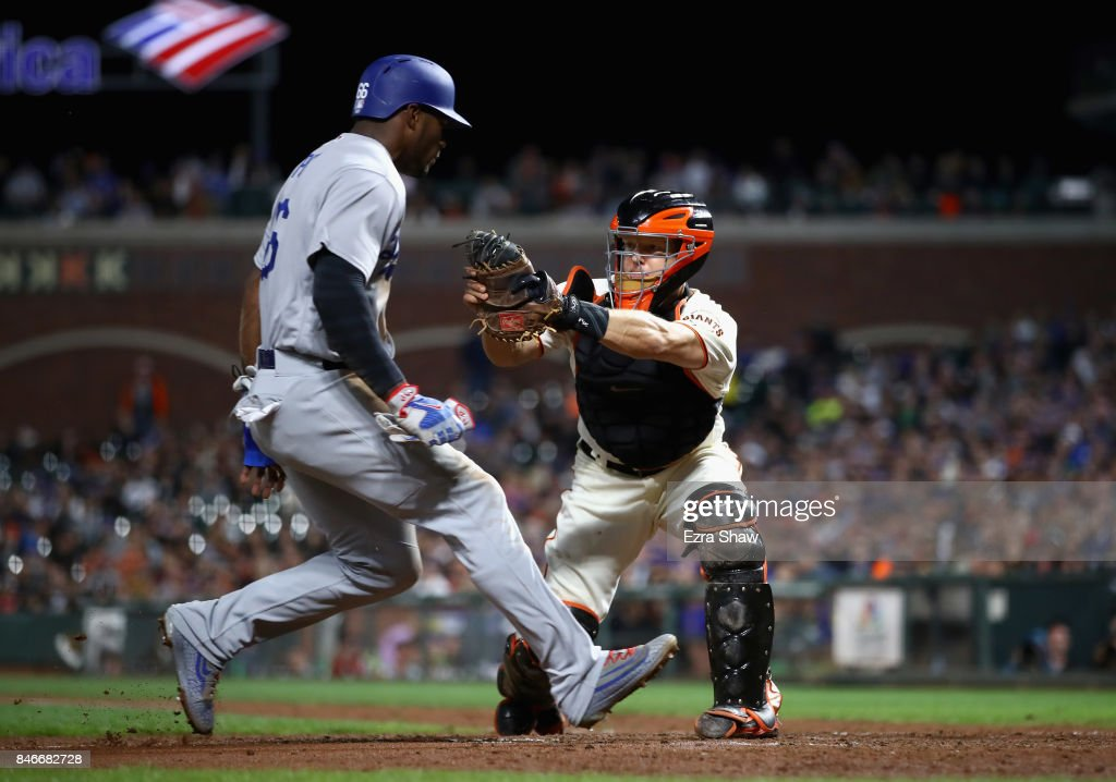 Yasiel Puig #66 of the Los Angeles Dodgers is tagged out by Nick Hundley #5 of the San Francisco Giants in the fourth inning at AT&T Park on September 13, 2017 in San Francisco, California.