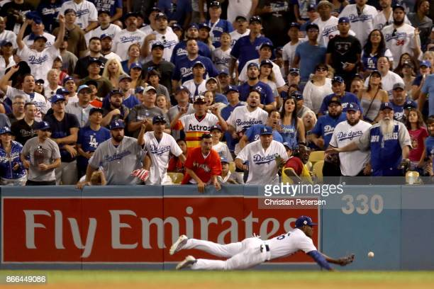 Yasiel Puig of the Los Angeles Dodgers is unable to catch a ground rule double hit by Alex Bregman of the Houston Astros during the eighth inning in...