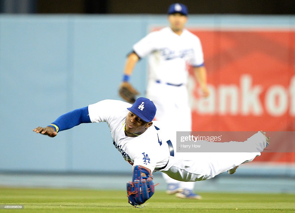 <a gi-track='captionPersonalityLinkClicked' href=/galleries/search?phrase=Yasiel+Puig&family=editorial&specificpeople=10484087 ng-click='$event.stopPropagation()'>Yasiel Puig</a> #66 of the Los Angeles Dodgers makes a diving attempt for a catch off the bat of Paul Goldschmidt #44 of the Arizona Diamondbacks during the 12th inning at Dodger Stadium on April 18, 2014 in Los Angeles, California.