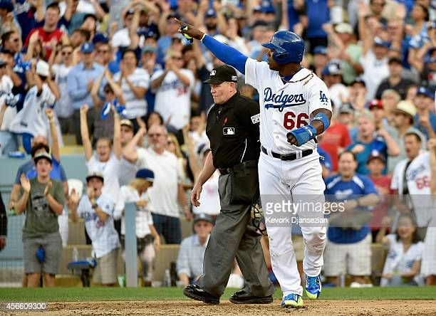 Yasiel Puig of the Los Angeles Dodgers points at teammate Hanley Ramirez after he scored on an RBI single in the third inning during Game One of the...