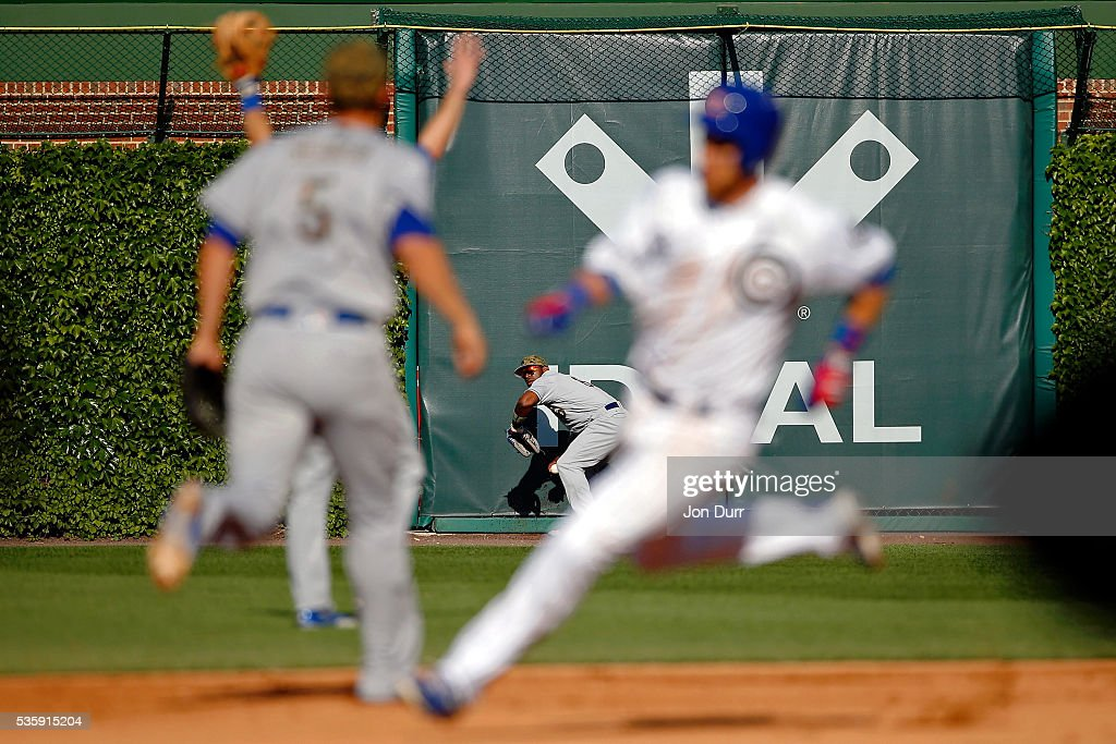 Yasiel Puig #66 of the Los Angeles Dodgers prepares to throw the ball to the infield as Ben Zobrist #18 of the Chicago Cubs rounds second base on his way to third base for a triple during the fifth inning at Wrigley Field on May 30, 2016 in Chicago, Illinois.