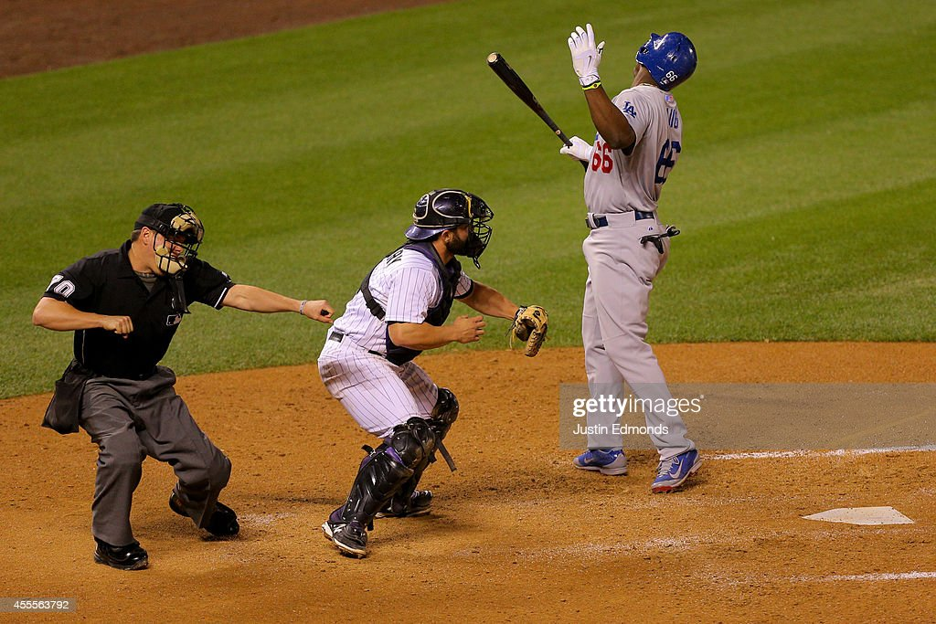 Yasiel Puig of the Los Angeles Dodgers reacts after being called out on strikes with the bases loaded by home plate umpire DJ Reyburn as catcher...