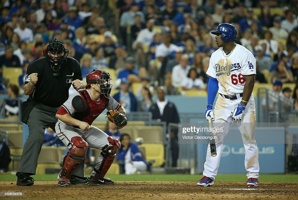 Yasiel Puig of the Los Angeles Dodgers reacts as MLB home plate umpire Bill Welke calls Puig out on strikes while catcher Miguel Montero of the...