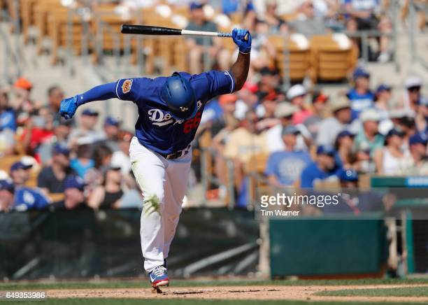 Yasiel Puig of the Los Angeles Dodgers reacts to hitting a ground ball in the fourth inning against the San Francisco Giants during the spring...
