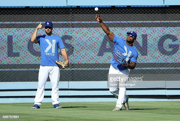 Yasiel Puig of the Los Angeles Dodgers right throws a ball back from right field as teammate Rob Segedin signals to the infield during batting...