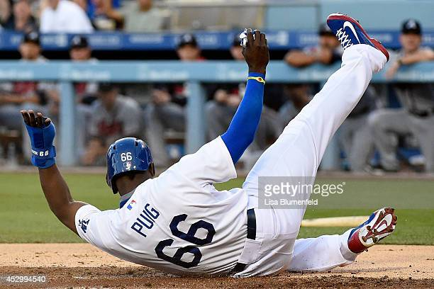 Yasiel Puig of the Los Angeles Dodgers scores in the first inning against the Atlanta Braves at Dodger Stadium on July 31 2014 in Los Angeles...