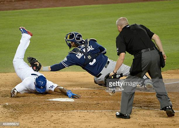 Yasiel Puig of the Los Angeles Dodgers slides around the tag of Yasmani Grandal of the San Diego Padres to score a run and trail 31 during the third...