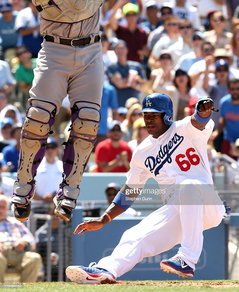 <a gi-track='captionPersonalityLinkClicked' href=/galleries/search?phrase=Yasiel+Puig&family=editorial&specificpeople=10484087 ng-click='$event.stopPropagation()'>Yasiel Puig</a> #66 of the Los Angeles Dodgers slides in to home to score a run as catcher <a gi-track='captionPersonalityLinkClicked' href=/galleries/search?phrase=Wilin+Rosario&family=editorial&specificpeople=5734314 ng-click='$event.stopPropagation()'>Wilin Rosario</a> #13 of the Colorado Rockies leaps for a high throw in the fifth ininng at Dodger Stadium on July 14, 2013 in Los Angeles, California.