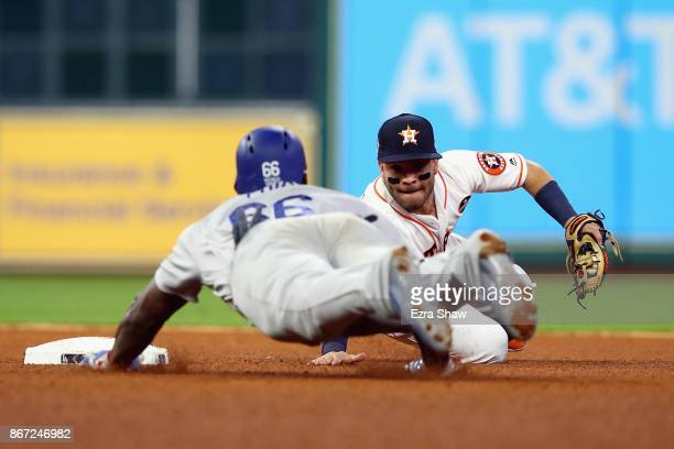 Yasiel Puig of the Los Angeles Dodgers slides in to second and is tagged out by Jose Altuve of the Houston Astros during the fourth inning in game...