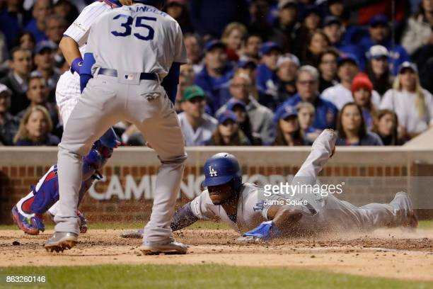 Yasiel Puig of the Los Angeles Dodgers slides into home plate to score a run as Cody Bellinger looks on in the fourth inning against the Chicago Cubs...