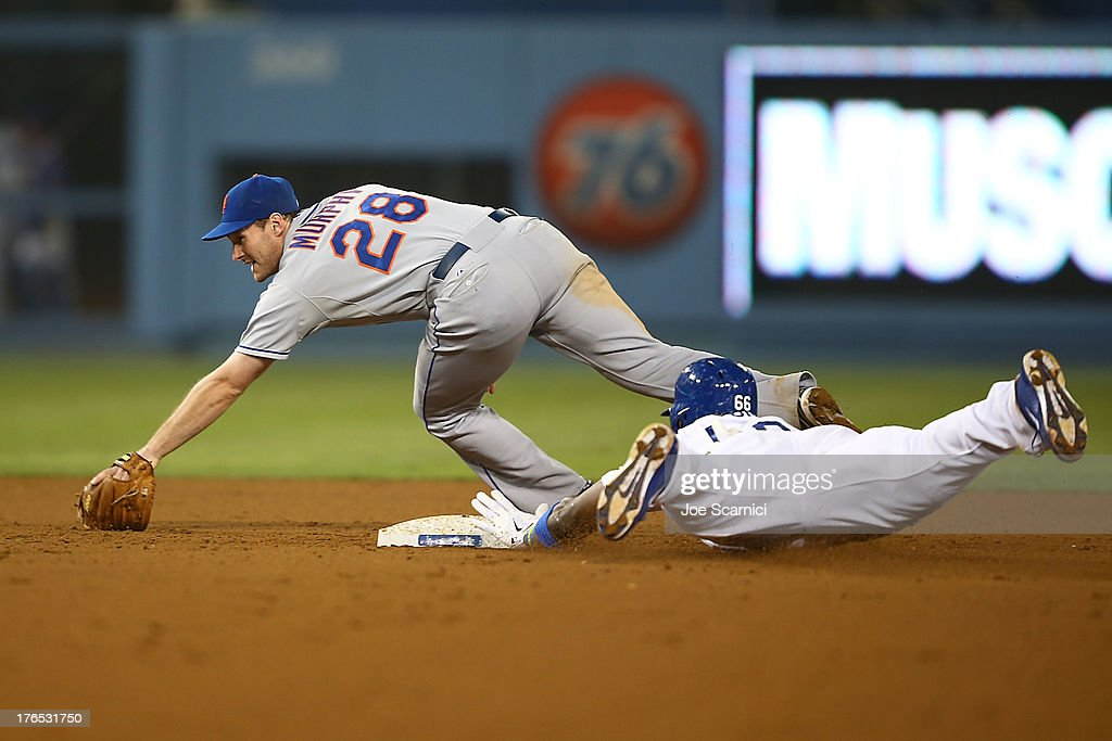 <a gi-track='captionPersonalityLinkClicked' href=/galleries/search?phrase=Yasiel+Puig&family=editorial&specificpeople=10484087 ng-click='$event.stopPropagation()'>Yasiel Puig</a> #66 of the Los Angeles Dodgers slides into second base after hitting a double on the ground to center field in the twelfth inning as Daniel Murphy #28 of the New York Mets tries to get him out at Dodger Stadium on August 14, 2013 in Los Angeles, California.